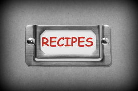 picture of recipe card  - A black and white image of a metal drawer label holder with a white card and the title Recipes added in red text - JPG