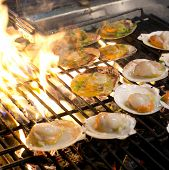 pic of flame-grilled  - Grilled scallops topped with butter garlic and parsley on flaming grill - JPG