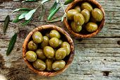 stock photo of olive branch  - Fresh olives and olive oil on rustic wooden background - JPG