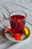 stock photo of tea bag  - Filter bag of hibiscus tea in a glass on white ceramic saucer with slice of lemon - JPG
