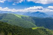 stock photo of naturel  - Sunlit mountain ridge with a shade from clouds - JPG