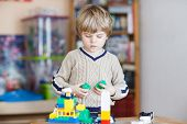foto of indoor games  - Adorable kid playing with lots of colorful plastic blocks indoor - JPG