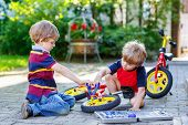 foto of four-wheel  - Two little boy friends twins learning to repair a bike and to to change a wheel - JPG
