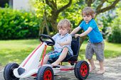pic of little kids  - Two happy active little kid and sibling boys having fun with toy race car in summer garden outdoors. Adorable brother pushing the car with younger child. Outdoor games for children in summer concept.