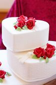 stock photo of cream cake  - Beautiful wedding cake in different colors with two levels and marzipan roses - JPG