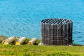 image of bluff  - An old wooden water container sits on a bluff next to the Pacific Ocean - JPG