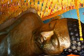 picture of recliner  - Huge reclining Buddha statue with flakes of gold leaf placed by pilgrims Phnom Kulen Cambodia - JPG