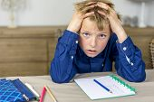 stock photo of struggle  - boy struggling with his homework holding his hands in his hair