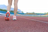 image of slender legs  - young fitness woman runner legs running on track - JPG