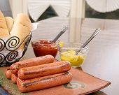 picture of condiment  - Grilled hot dogs on a stacked on a plate ready to serve with condiments ketchup and mustard and buns - JPG