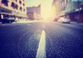 picture of sunrise  - an empty street scene during sunrise or sunset of an urban cityscape toned with a retro vintage instagram filter effect app or action - JPG