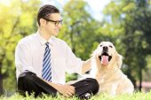 stock photo of dog park  - Smiling young businessman with his dog sitting on grass in a park - JPG