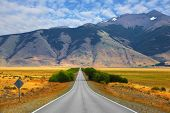 image of steppes  -  Smooth asphalt road passes between the yellow plains to the distant mountains - JPG