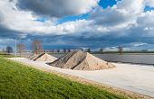 foto of sand gravel  - Storage and handling of sand and gravel on the banks of a Dutch river - JPG