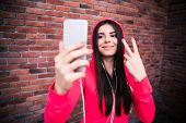 image of sportive  - Smiling young sportive woman in headphones making selfie photo with brick wall - JPG