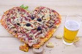 stock photo of olive shaped  - Heart shaped pizza and and pastry with a glass of beer on wooden table - JPG