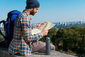 stock photo of concentration man  - Concentrated young man sitting near backpack and looking through a map - JPG