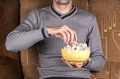 picture of popcorn  - Young guy watching TV on the couch and eating popcorn - JPG