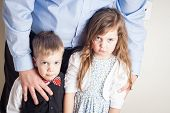 image of brother sister  - brother and sister held by their father with guilt on their faces great parenting image - JPG