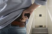 pic of bodyguard  - Bodyguard with gun protects client against an s water closet door background  - JPG
