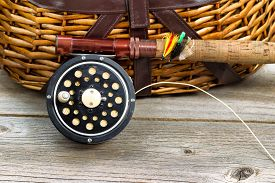 stock photo of fly rod  - Close up of an antique fly fishing reel rod and artificial flies in front of creel with rustic wood underneath - JPG