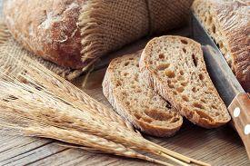picture of fresh slice bread  - Fresh bread slice and rye ears on rustic table - JPG