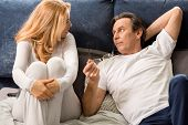 Upset Middle Aged Couple Talking, Looking At Each Other And Lying On Bed At Home poster