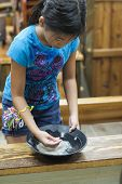 picture of gold panning  - Close up of an Asian girl panning for gems - JPG