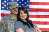 stock photo of soldiers  - Happy young couple in front of the american flag with the young man in military uniform - JPG