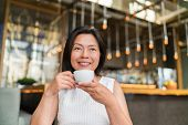 Asian middle aged woman drinking cappuccino coffee at high end fancy cafe. Chinese businesswoman enj poster