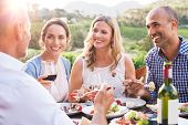 Group of mature people eating together in a vineyard in a summer day. Happy woman sipping wine while poster