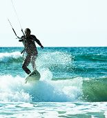 Kiteboarder riding wave