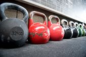 Long Receding Row Of Kettlebell Weights In A Gym poster