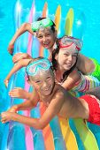 Three, smiling, happy children on a large float in a swimming pool.
