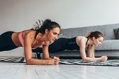 Two Fit Women Doing Plank Exercise On Floor At Home Training Back And Press Muscles, Sport, Fitness  poster