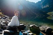 Romantic Groom And Bride In Beautiful White Wedding Dress Standing On The Stony Shore Of The Morskie poster