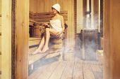 Young Beautiful Woman Relaxing In The Finnish Sauna Wrapped In Towel. Interior Of Finnish Sauna, Cla poster