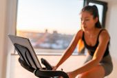 Home fitness fit woman exercising on smart stationary bike at home gym class watching screen online  poster