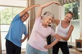Senior couple doing exercise at home with physiotherapist. Mature gym trainer helping elderly man an poster