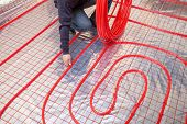 Pipefitter installing system of heating. Heating system and underfloor heating.  poster