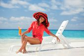 Fashion woman drinking cocktail on the beach. Happy island lifestyle. White sand, blue cloudy sky an poster