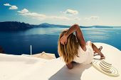 Luxury travel vacation woman looking at view on Santorini island in Greece. Amazing view of sea and  poster