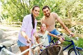 family, leisure and people concept - happy mother, father and little daughter with bicycles taking p poster