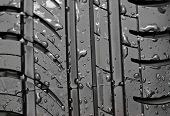 Close-up of car tire with with water drops to background