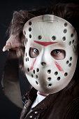 stock photo of machete  - Horrible maniac in mask with machete posing over dark background - JPG