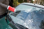 stock photo of ice-scraper  - A woman is scraping the frost from het windshield - JPG