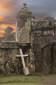 stock photo of entryway  - An old cement cross leaning up against the walls of an ancient Spanish fort that is slowly crumbling in the tropical heat of Panama - JPG