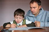 Father helping son doing homework