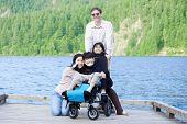 Disabled Boy In Wheelchair Surrounded By Family On Lake Pier