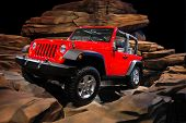 Red Jeep Climbing Rocks